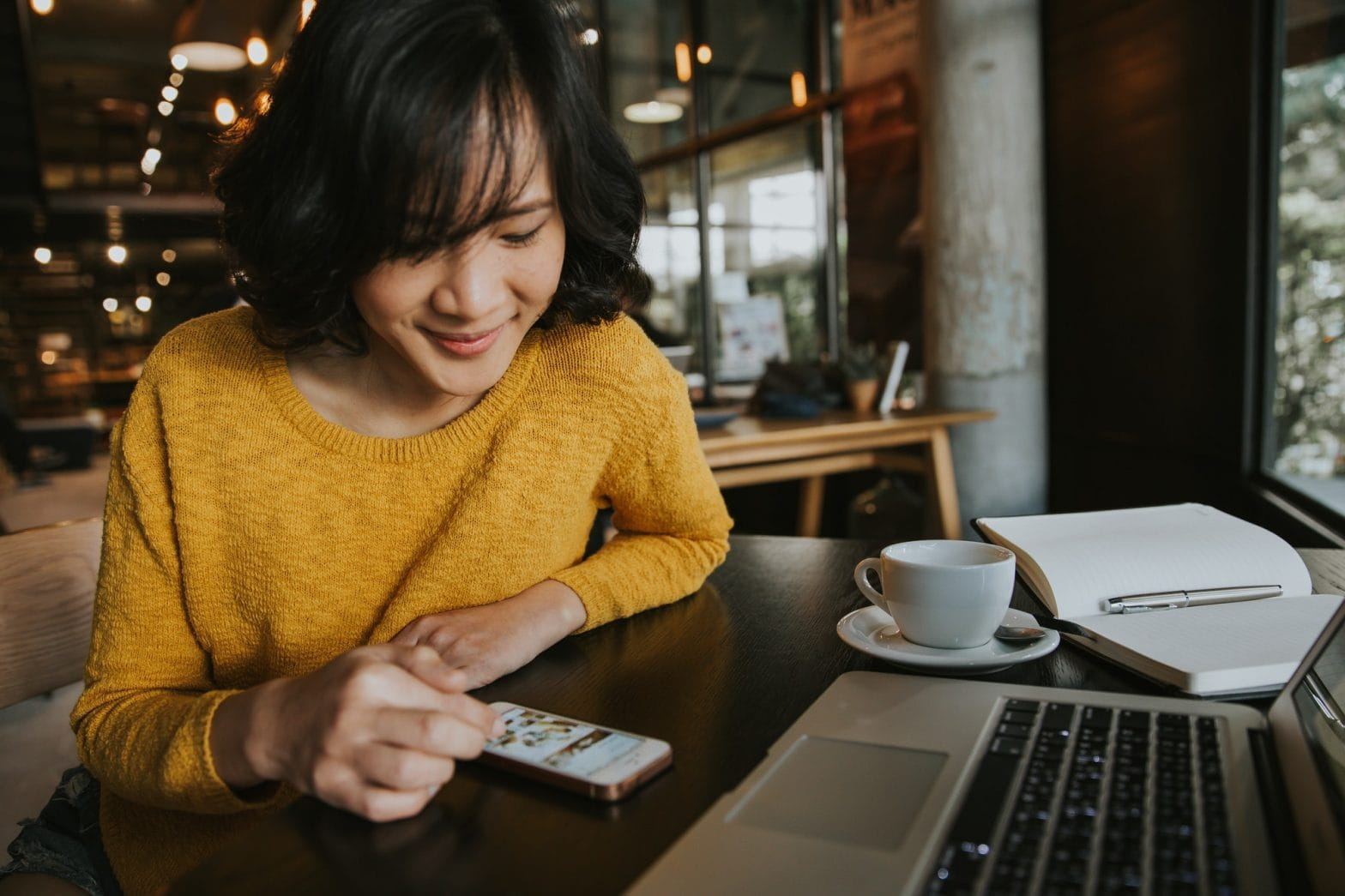 Young woman sitting in coffee shop using smartphone with happy face. business, coffee, smartphone,